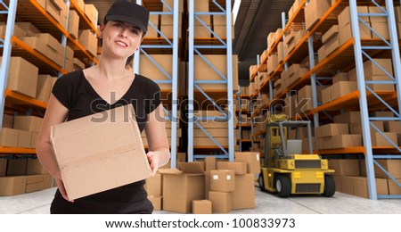 Female courier carrying a parcel in a distribution warehouse - stock photo