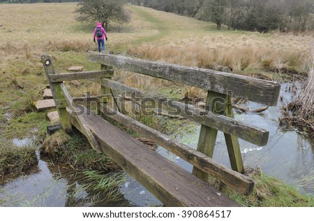 Female Crossing a Wooden Bridge with a Stile over Bletch Brook, near the Rural Village of Tissington, within the Peak District National Park, Devon, England, UK - stock photo
