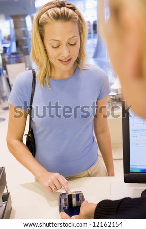 Female customer at checkout enetring PIN number - stock photo