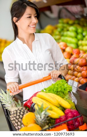 Female customer at the supermarket with a shopping cart - stock photo