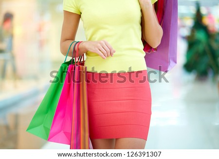 Female customer carrying colorful shopping bags - stock photo