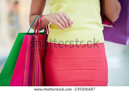 Female customer in smart casual carrying colorful paperbags - stock photo