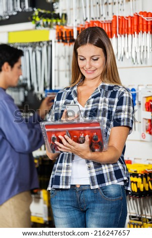 Female customer scanning pliers set through mobile phone with man in background at hardware store - stock photo
