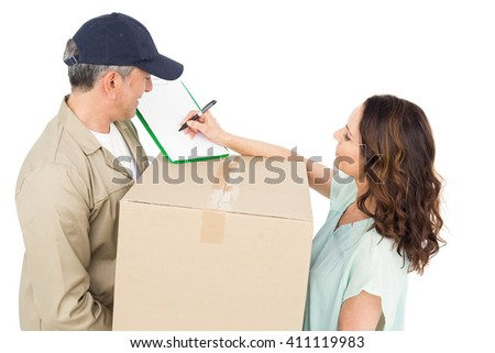 Female customer signing on paper with delivery man standing on white background - stock photo