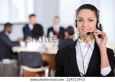 Female customer support operator with headset and smiling, people group in background at modern bright office indoors - stock photo