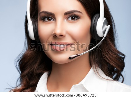 Female customer support phone operator in headset, against grey background. Consulting and assistance service call center. - stock photo