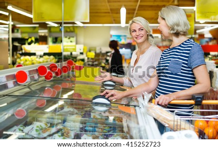 Female customers standing near display with a frozen food in a supermarket  - stock photo