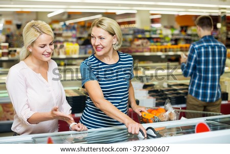Female customers standing near display with frozen food at the supermarket  - stock photo