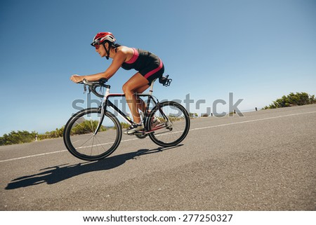 Female cyclist on a country road training for competition. Young woman riding bicycle down hill. - stock photo