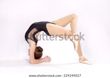 Female dancer in a black bathing suit posing arching back - stock photo