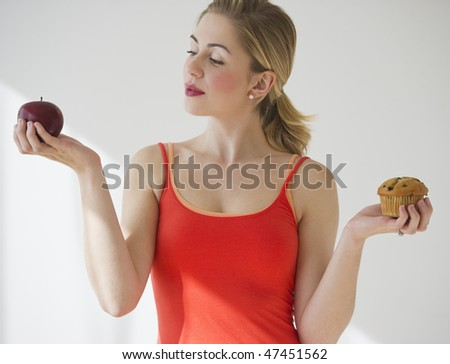 female deciding between eating an apple or a muffin - stock photo