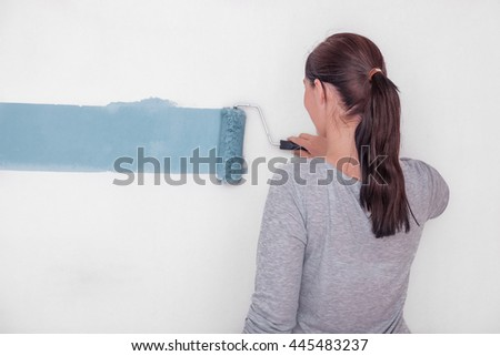 female decorating with color a wall - stock photo