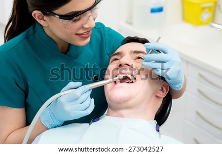 Female dental assistant treat male patient in clinic - stock photo