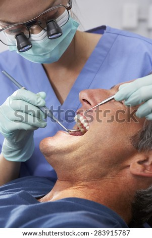 Female Dentist Giving Male Patient Check Up - stock photo