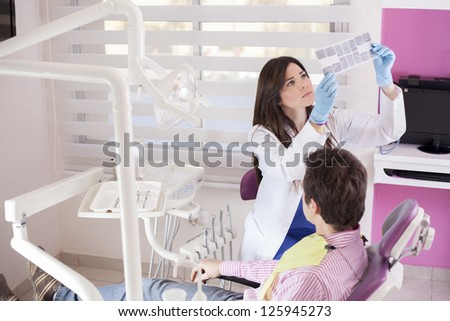 Female dentist reviewing the x-rays of a patient - stock photo