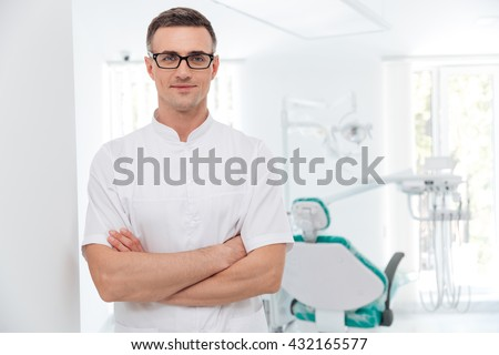 Female dentist standing with his hands crossed and looking at camera - stock photo