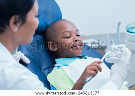 Female dentist teaching boy how to brush teeth in the dentists chair - stock photo