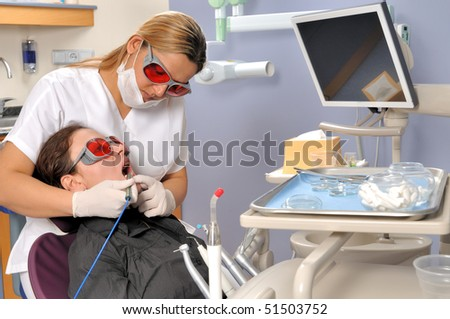 Female dentist whitening teeth with multi purpose laser - a series of DENTAL related images. - stock photo