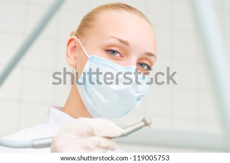 female dentists in protective mask holds a dental drill, the doctors at work - stock photo