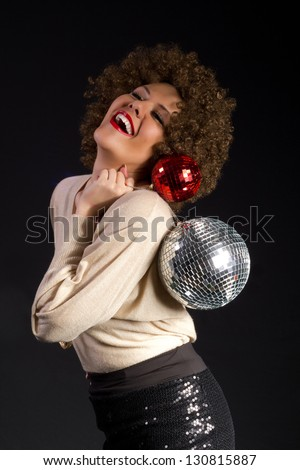 Female disco dance party girl holding two shiny disco balls on black background - stock photo
