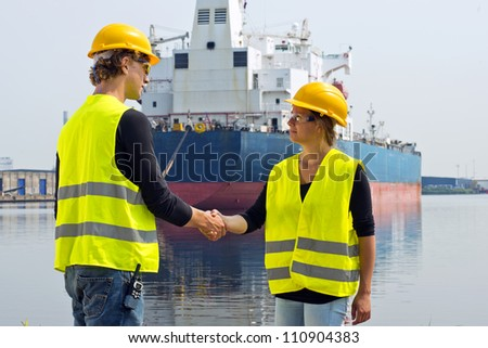 Female docker shaking hands with a male coworker in an industrial harbor, in front of a huge freight ship - stock photo