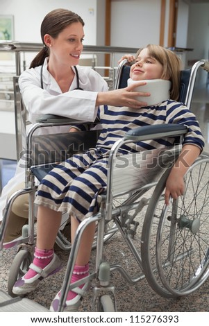 Female doctor adjusting childs neck brace in wheelchair in hospital corridor - stock photo