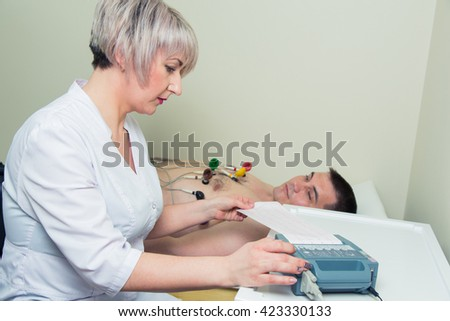 Female doctor analyzing ECG electrocardiogram of patient in hospital. - stock photo