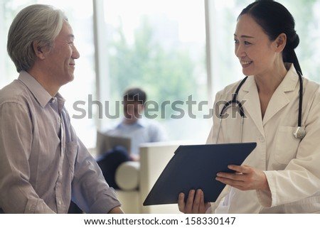 Female doctor and patient discussing medical record in the hospital - stock photo