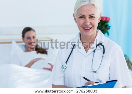 Female doctor and pregnant woman smiling at camera in hospital - stock photo