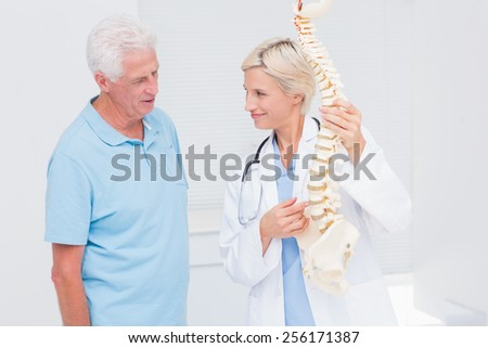 Female doctor and senior patient discussing over anatomical spine in clinic - stock photo