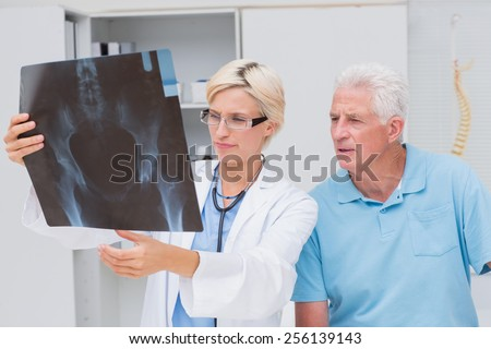 Female doctor and senior patient examining x-ray in clinic - stock photo