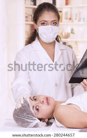 Female doctor checking xray of a young girl patient thats's lying down - stock photo
