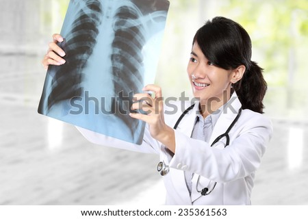 Female doctor examining an x-ray in the laboratory - stock photo