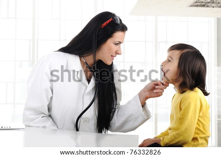 Female doctor examining child with tongue depressor - stock photo