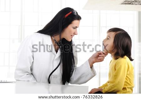 Female doctor examining child with tongue depressor - stock photo