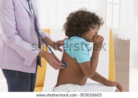 Female doctor examining little child boy - stock photo