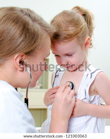 Female doctor examining little girl with stethoscope - stock photo