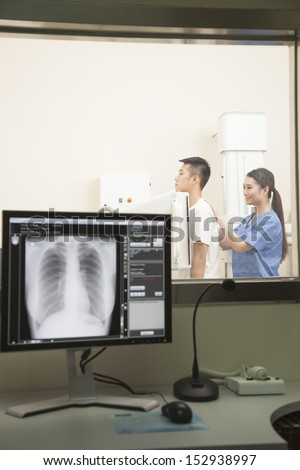 Female Doctor Examining Male Patient's Mid Section With X-ray Machine - stock photo