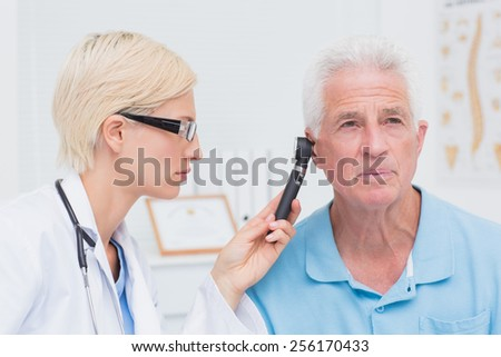Female doctor examining male patients ear with otoscope in clinic - stock photo