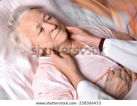 Female doctor examining old woman in the hospital - stock photo