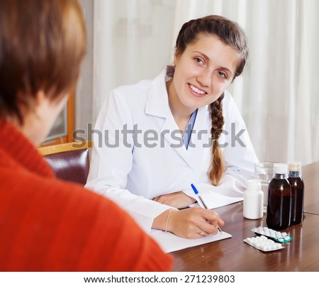 Female doctor examining patient  at table - stock photo