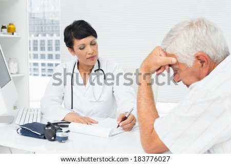 Female doctor explaining reports to worried senior patient at medical office - stock photo