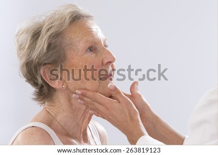 Female doctor feeling female patient's neck for swollen glands. - stock photo