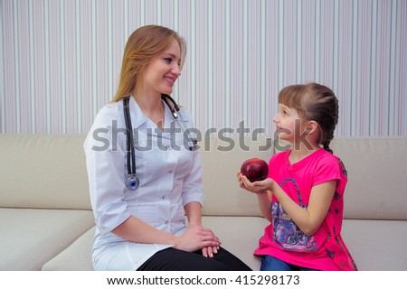 Female doctor gives a girl an apple - stock photo