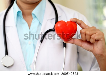 Female doctor holding a red heart - stock photo