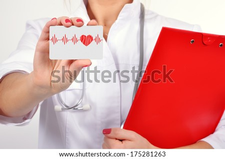 female doctor holding business card with heartbeat - stock photo