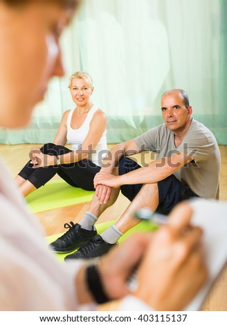 Female doctor keeping eye at elderly couple during training at gym. Focus on man - stock photo
