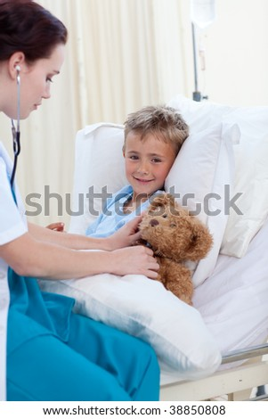 Female doctor listening to a child chest and a teddy bear with stethoscope in bed - stock photo