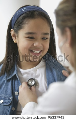 Female doctor listening to young girl's heartbeat - stock photo