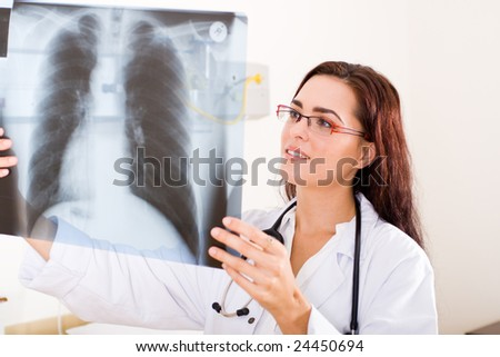 female doctor looking at a lungs or torso xray - stock photo